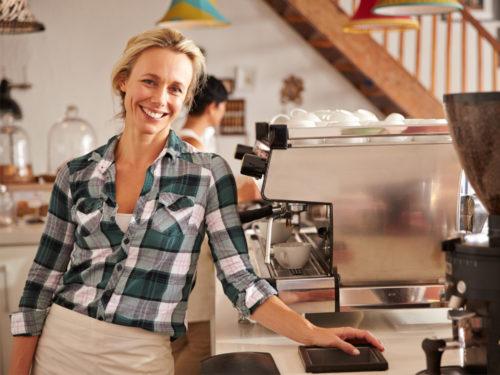 Lächelnde Frau in einem Café oder Restaurant, die das Kassensystem Dinapay verwendet.