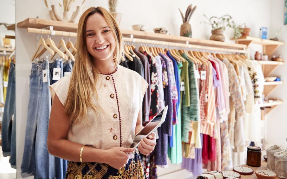 Junge Frau in ihrer Kleiderboutique mit dem Dinapay-Kassensystem auf dem Tablet