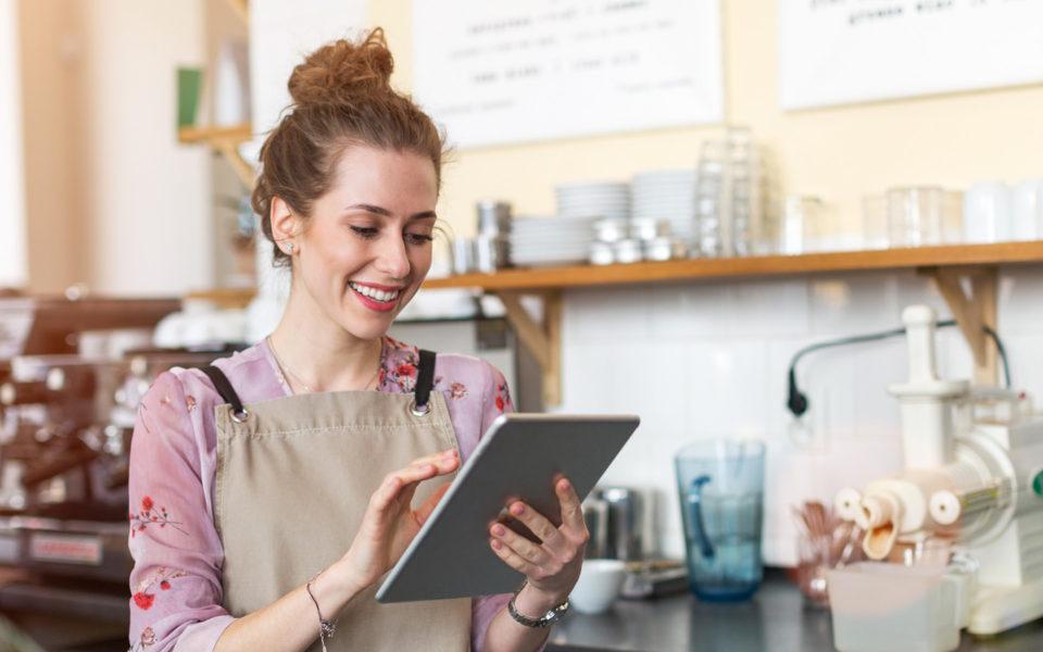Junge Frau in der Gastronomie bedient das Kassensystem Dinapay auf dem Tablet